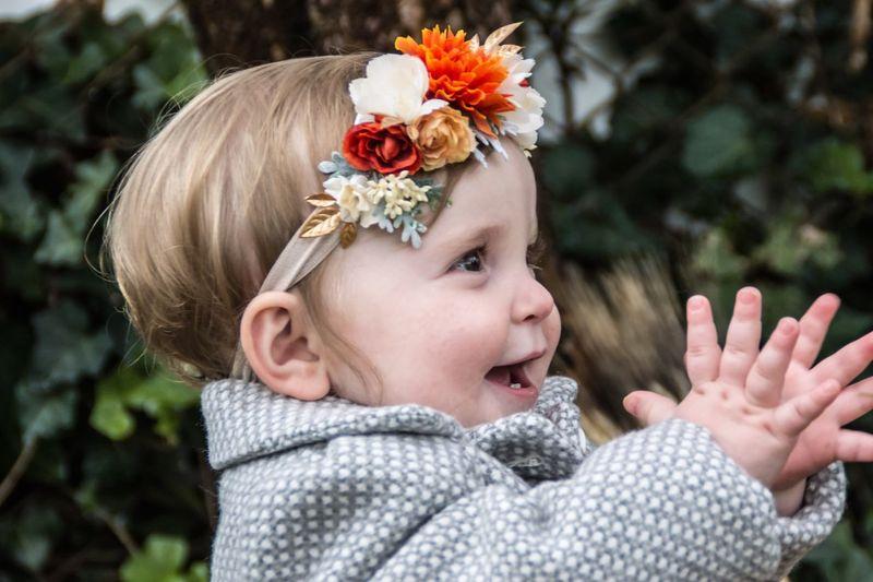 Cute baby girl applauding while wearing flower headband