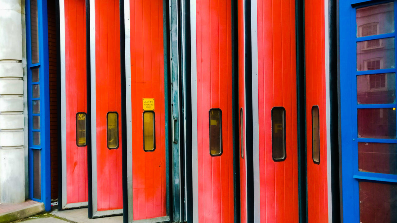no people, multi colored, red, architecture, side by side, in a row, full frame, built structure, indoors, day, closed, backgrounds, building, pattern, door, sunlight, metal, repetition