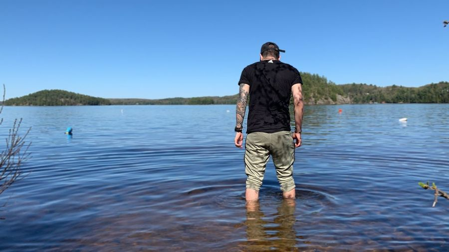 Man standing in lake against clear blue sky