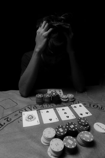 Man with head in hands gambling against black background