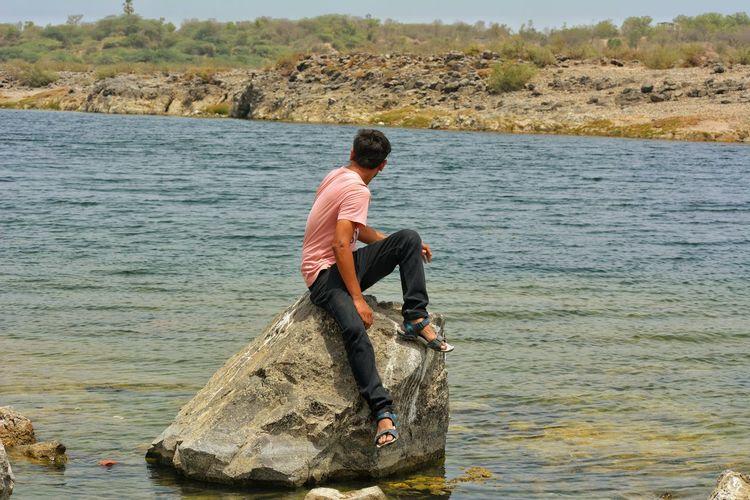 Man Sitting On Rock In Sea