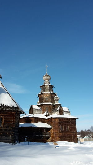 Old wooden church in the open air museum of Suzdal', Russia Snow Cold Temperature Architecture Winter Built Structure Sky Building Exterior Building Nature Religion No People Day Place Of Worship Belief Spirituality Blue Clear Sky Travel Destinations Outdoors Spire  Open Air Museum Church Wooden Church  Ancient Architecture Church Architecture