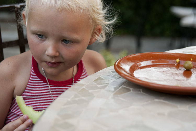 Young girl sitting by the table eating melon. Child Childhood Cute Food Food And Drink Girls Innocence One Person Sitting