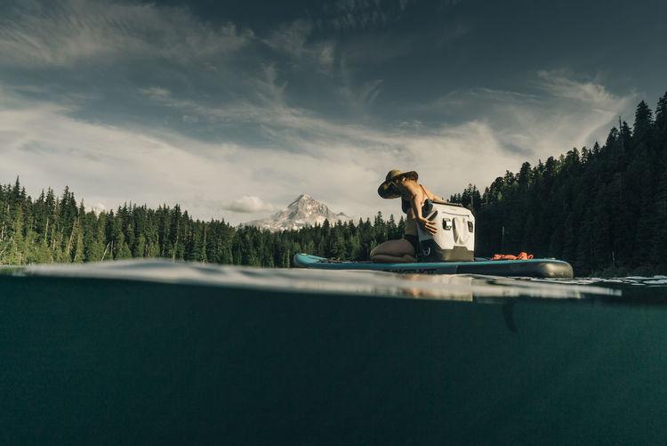 Man in swimming pool by lake against sky