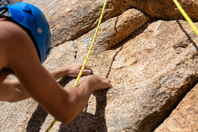 Close up hands of young man climber in a crack while climbing a wall on a sunny day. Close Up Hand Cliff Climbing Climb Holding Powder Handhold Rock Young Mountain Hanging Strong Finger Outdoor Sport Stone Grip Difficult Exercise Magnesium Athlete Mountaineer Leisure Activity Magnesia