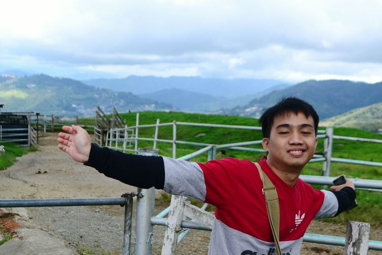 Portrait of young man standing on railing against mountains