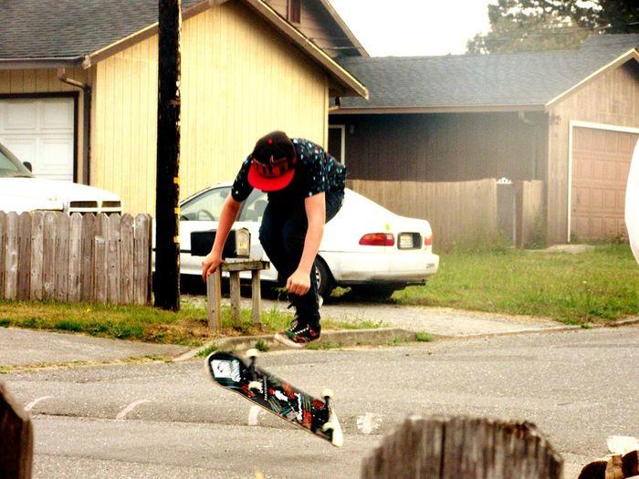 Man skateboarding on street against houses