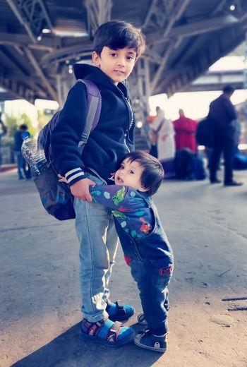 Full length portrait of siblings standing on railroad station platform