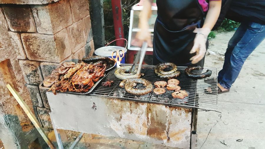 Midsection Of Woman Preparing Meat On Barbeque Grill