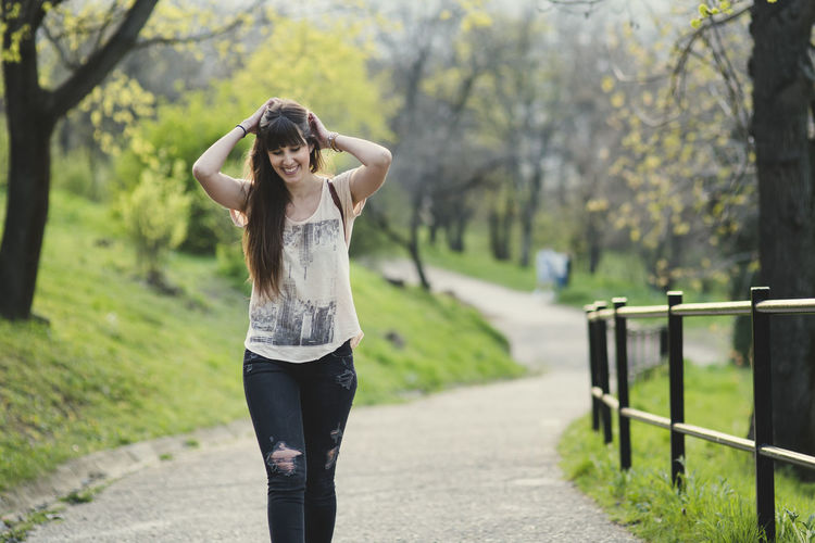 beautiful young woman walking outside in the girl with long brown hair smiling Adult Arms Raised Beautiful Woman Casual Clothing Day Focus On Foreground Footpath Front View Hairstyle Human Arm Leisure Activity Lifestyles Looking At Camera Nature One Person Outdoors Plant Portrait Real People Standing Tree Young Adult Young Women