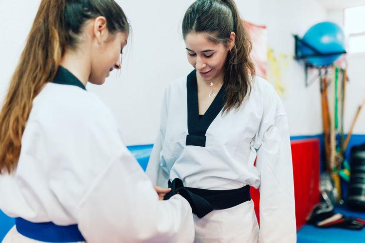 Young women wearing belt during taekwondo practice
