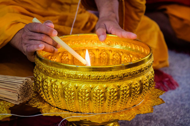 Midsection of man holding candles in temple