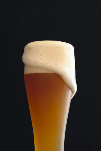Close-up of beer glass against black background