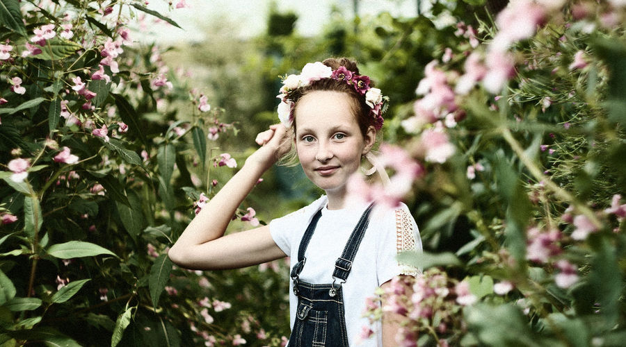 Portrait of smiling young girl standing amidst plants