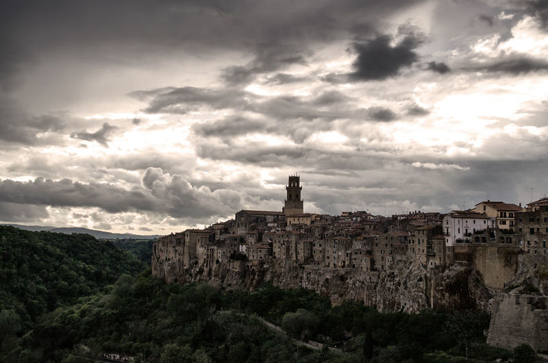 Buildings against cloudy sky at pitigliano