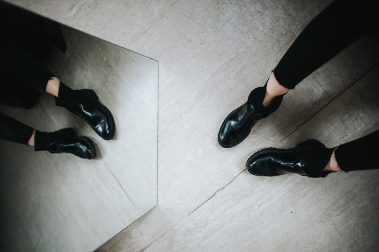 Low section of person standing by mirror with reflection on floor