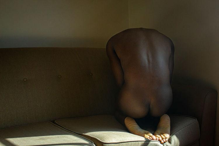 Naked man sitting on sofa at home