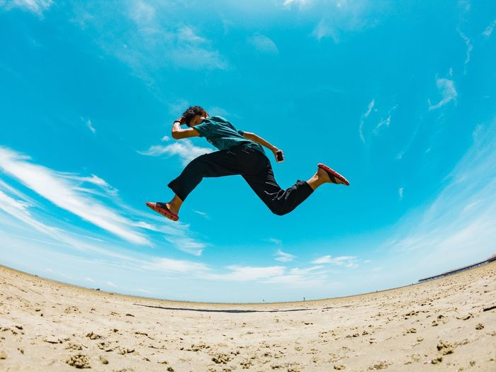 Low angle fish-eye lens shot of man jumping at beach against sky during sunny day