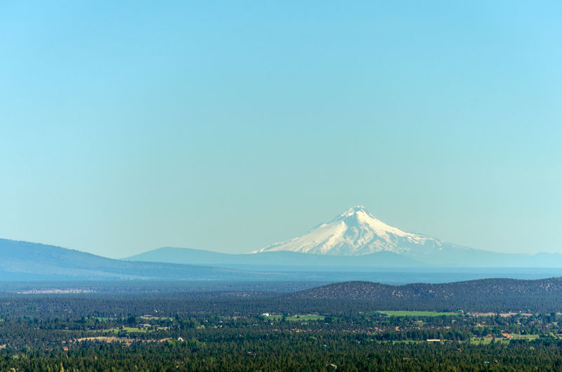 Scenic view of landscape with mt hood in background against clear blue sky