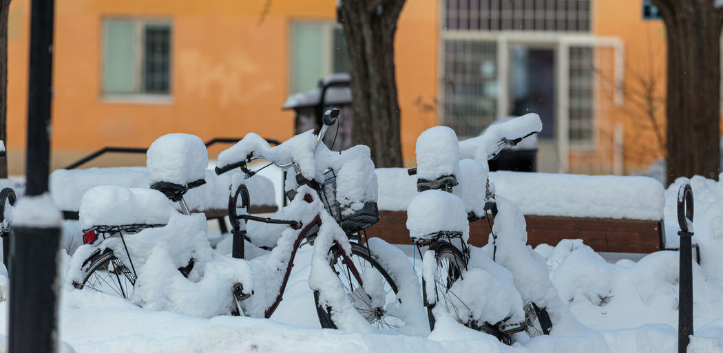 Snow covered fence by building in city during winter