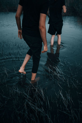 Low section of couple walking in lake
