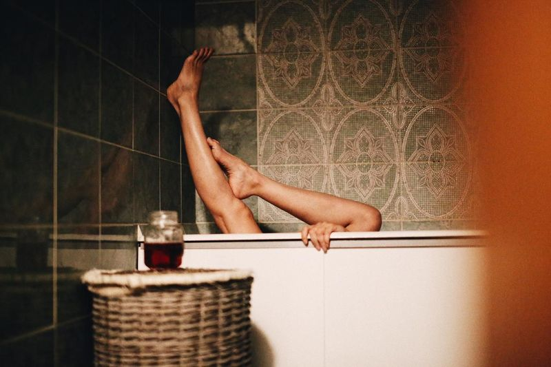 Low section of man with arms raised in bathroom