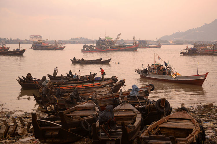 Fishing boats moored at harbor during sunset