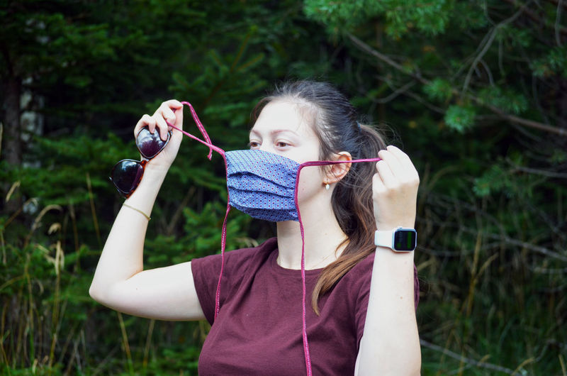 Portrait of young woman with brown ponytail in a colorful patterned face mask on a nature background