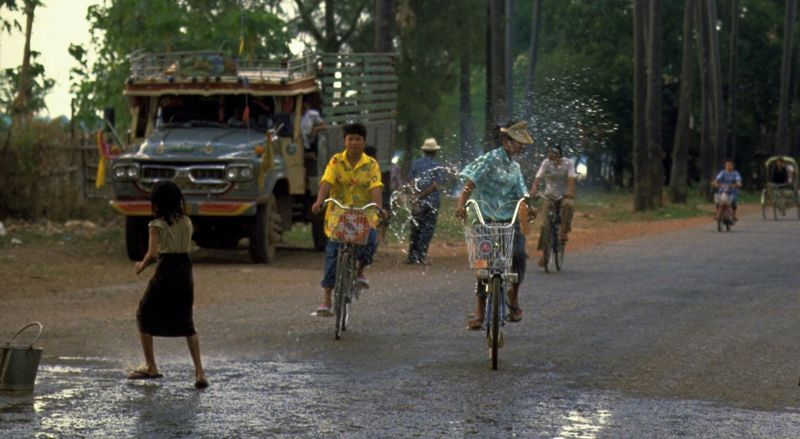 Songkran In Vientiane, Laos. Children playing with water at the Songkran water splashing festival in Vientiane, Laos. http://pics.travelnotes.org/ ASIA Children Horizontal Kids Playing Songkran Songkran Festival Travel Travel Photography Trees Vientiane Asian Girl Candid Cycling Cyclists Day Laos Outdoors People Playing Real People Road Splashing Street Photography Transportation Water
