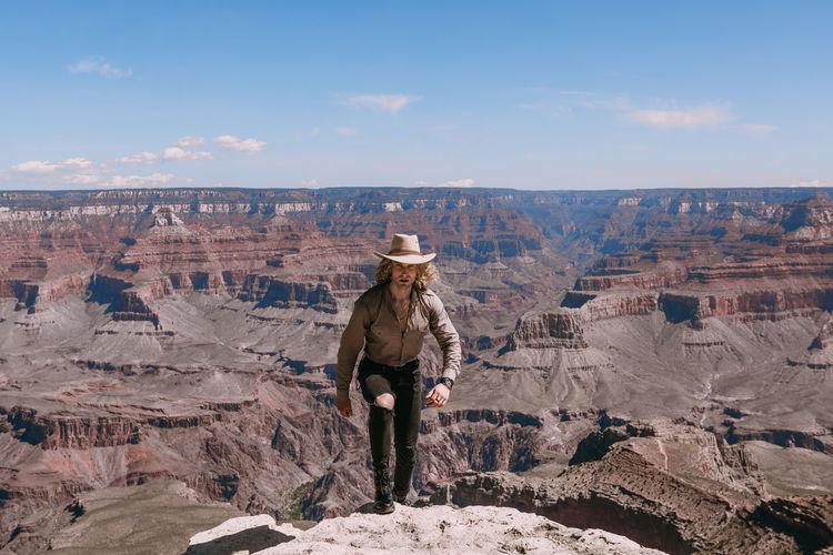Man wearing hat walking on mountain against sky