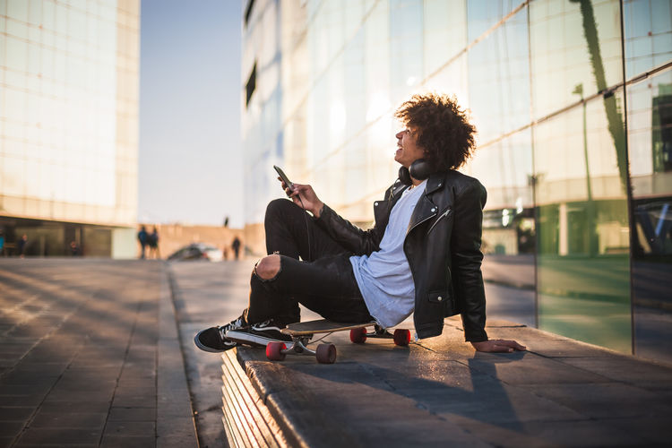 Side view of young man using smart phone against sky