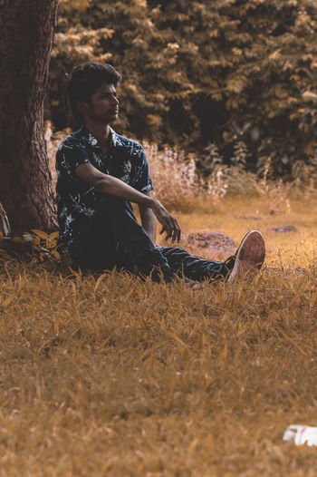 Young man looking away while sitting on land