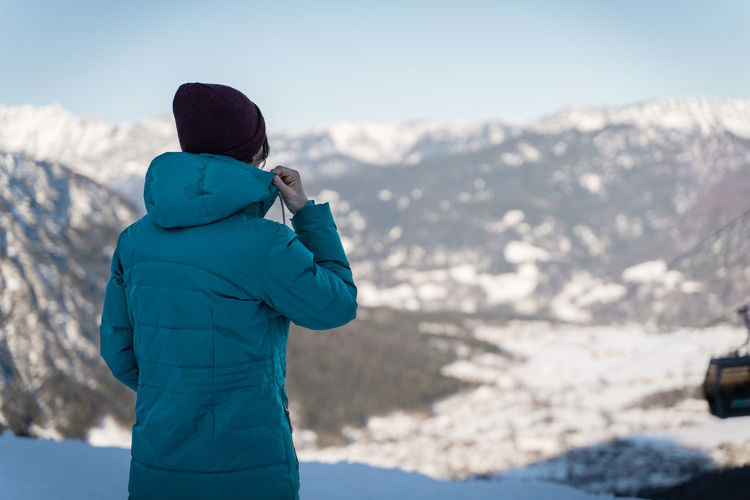Rear view of woman looking at snowcapped mountain