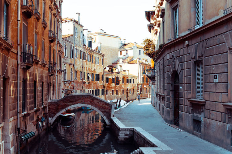 Arch bridge over channel amidst buildings against clear sky