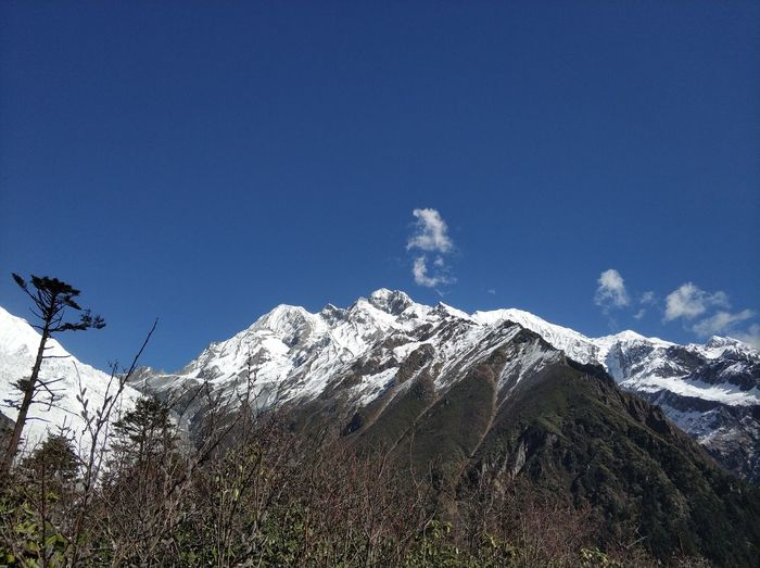 Low Angle View Of Snowcapped Mountains Against Blue Sky
