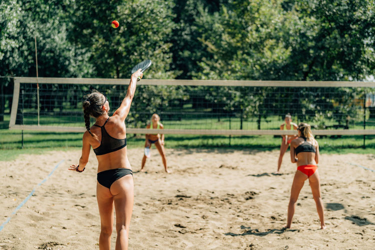Beach tennis player serving the ball
