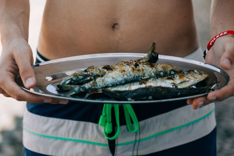 Midsection Of Man Holding Grilled Fish In Plate