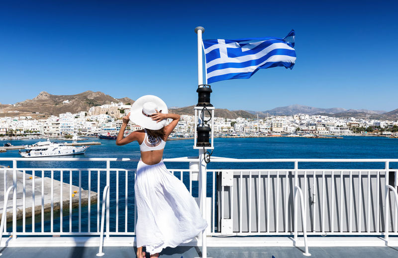 Woman in white dress arriving on a ferry boat at Naxos Island, Greece Blue Cyclades Day Dress Ferry Flag Greece Greek Hat Holiday Island Model Nautical Vessel Naxos Outdoors Railing Sea Sky Sunlight Transportation Travel Destinations Traveling Water White Woman