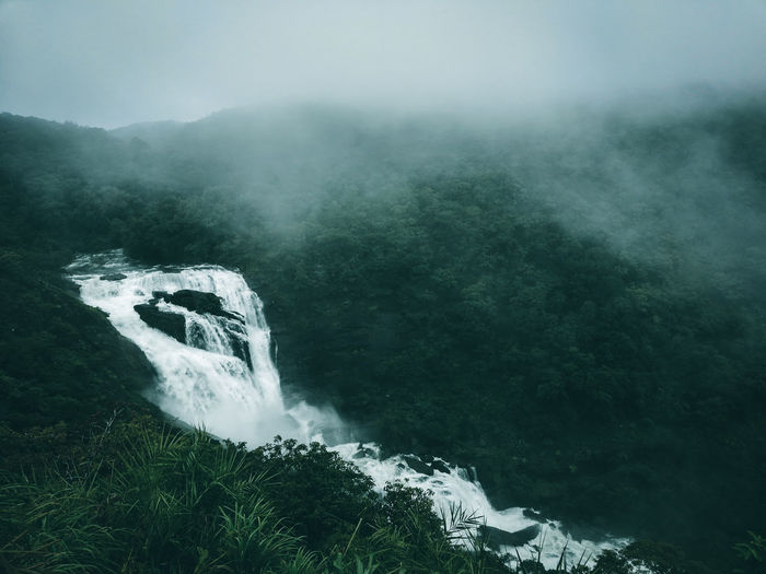 Scenic view of waterfall during foggy weather