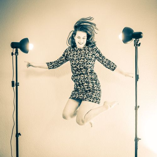Smiling Woman Jumping By Illuminated Lights In Studio