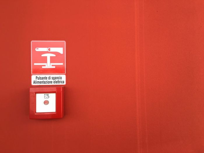 Danger sign and push button on red wall