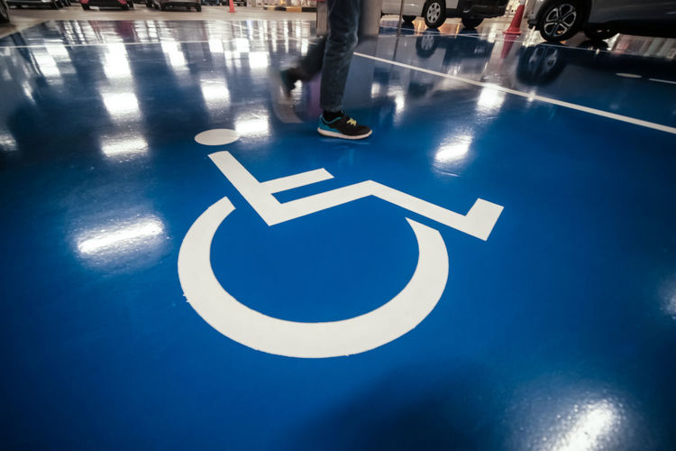 Low section of man walking on disabled sign over blue floor
