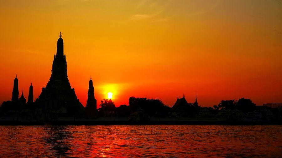 Silhouette of temple building against sky during sunset