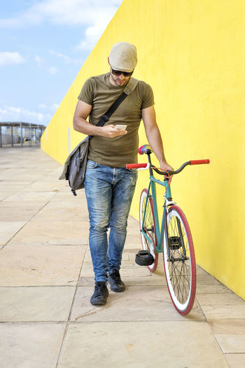 Front view of a young trendy man with a fixed bike wearing casual clothes while using a mobile phone against a yellow wall outdoors in a sunny day One Person Full Length Real People Bicycle Casual Clothing Lifestyles Transportation Leisure Activity Front View Yellow Day Mode Of Transportation Men Architecture Land Vehicle Adult Outdoors Standing Sport Jeans Young Man Hipster Trendy Fashionable Hat T-shirt Shoulder Bag Sunglasses Mobile Phone Smartphone Using Phone Standing Retro Fixie Vintage Looking Away Jeans