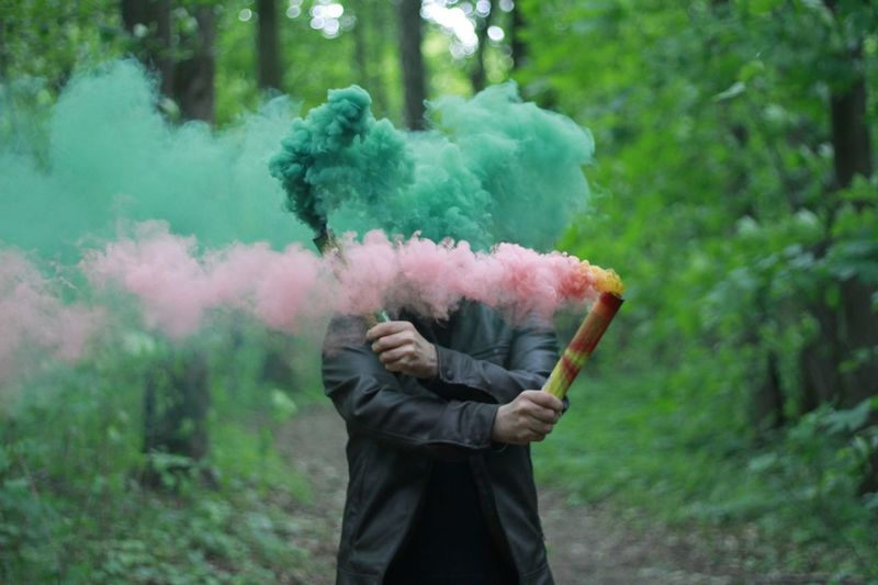 Man holding distress flare while standing in forest