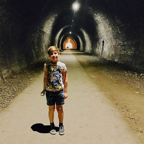 Young boy standing looking to camera in large tunnel Real People Disc Fun Happiness Summertime Exploring Holiday Boy Tunnel Dark Full Length Childhood One Person Real People Tunnel The Way Forward Casual Clothing People Outdoors Standing Day Leisure Activity