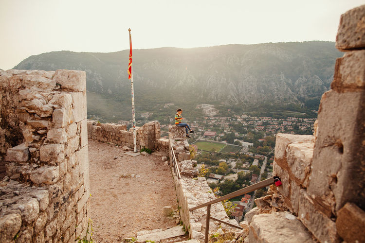 Woman sitting on retaining wall against mountain in town