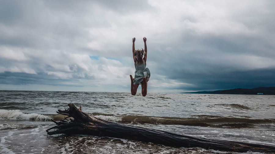Rear view of woman jumping at beach against cloudy sky