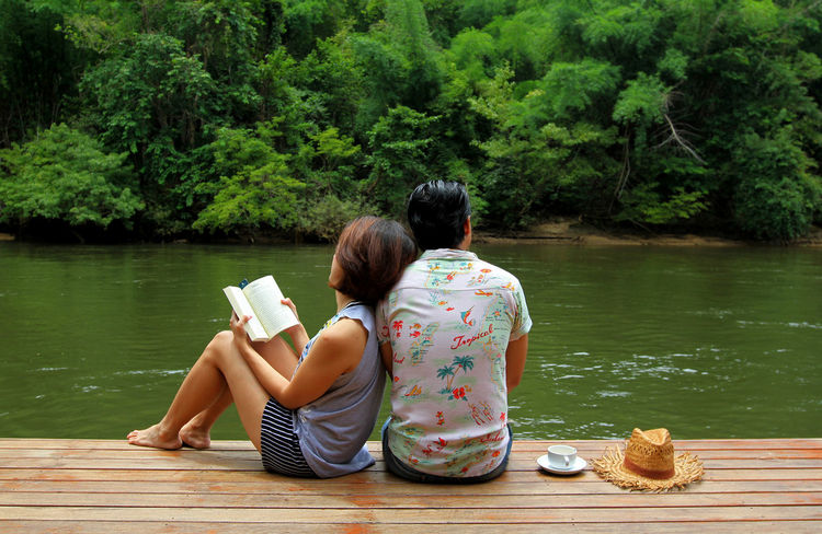 Happiness young couple in love relaxing enjoying river view and forest sitting and reading book together on the wood floor with cup of coffee and straw hat Chill Out Couple Happiness Lover Beside Cup Of Coffee Fresh Husband And Wife Lake Love Lovely Nature Outdoors People Reading & Relaxing Real People Relaxation River Sitting Summer Sweet Togetherness Two People Vacations Water