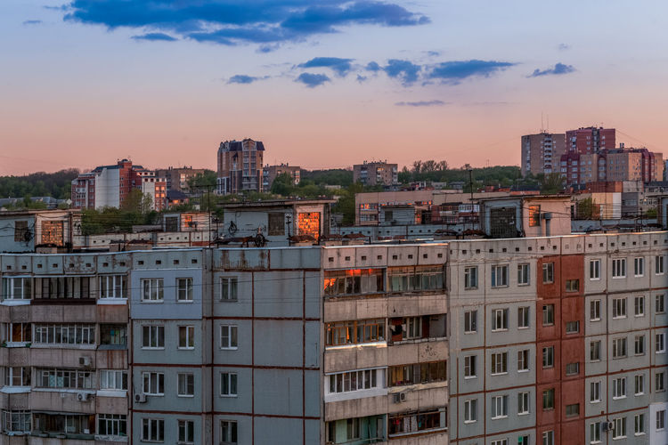 Windows, roofs and facade of an mass apartment buildings in russia at evening